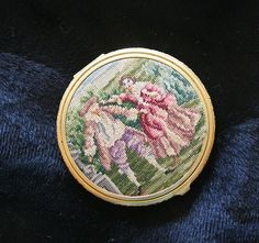 This is a gorgeous antique Austrian petit point needlepoint mirrored compact This set dates from the 1930s to 1940s and features a courting couple on the outside- a woman in an elaborate rose and magenta dress and her suitor in powdered wig, fancy hat, pantaloons, frock coat and