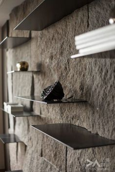 Thin shelves slotted straight into a rock wall - it doesn't get much more minimalist gorgeous than that!