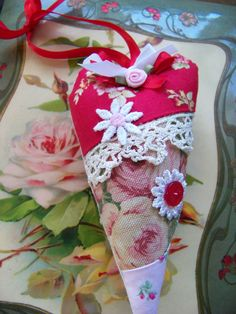 Fabric heart, handmade from vintage cotton fabrics, a vintage button, vintage lace trim, and flowers, and topped with a ribbon rose and ribbon hanger