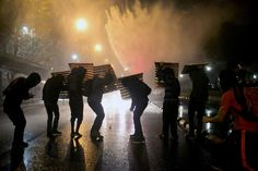 Demonstrators take cover as a jet of water is released during a rally against police violence and in support of Rodrigo Aviles, a student injured on May 21 following a protest march, in Santiago, May 28, 2015. REUTERS/Pablo Sanhueza