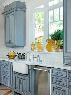 Painted Cabinets and Farmhouse Sink A beautiful blue glaze covers the new cabinets in this kitchen, playing perfectly off the graining in the marble countertops. The large white farmhouse sink sits below a trio of windows, allowing a perfect view to the o Kitchen Cabinets Decor, Farmhouse Kitchen Cabinets, Kitchen Cabinet Design, Painting Kitchen Cabinets, Kitchen Redo, New Kitchen, Kitchen Remodel, Kitchen Sinks, Kitchen White