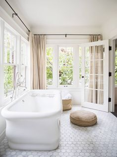 Underused sun room? Why not turn it into a soak-tub heaven complete with oversize honeycomb tiles and 360-degree curtains?