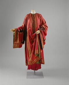 This Fortuny-designed maroon caftan, or djellaba, is based on Asian and North African forms.  Fortuny preserves the length of the fabric panels without interruptions of tailoring, not because he is averse to cutting the textile but rather to advance the caftan as an apparel type.  As in the traditional Asian garment type, the sleeves of the Fortuny coat extend to cover the wearer's hands.