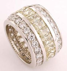 Make a statement with this cubic zirconia full eternity band set with .25 carat each radiant emerald cut canary cz stones with small round stones above and below. This stunning ring can be set with the cubic zirconia stone color of your choice and can be created in 14k yellow and white gold. From Orleansjewels.com