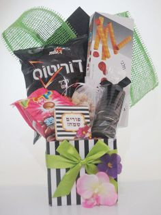 Wow your friends or family with this designer inspired arrangement, overflowing with delicacies.  Includes: Box of wafer rolls Spicy, hot Doritos Kliks chocolate covered cookie bites Coated peanuts with sesame seeds Chocolate sandwich cookies And a custom striped with flowers Purim Sameach cookie