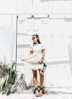 Blogger Collage Vintage wears a white lace mini dress, studded black heeled sandals, a crossbody bag, and round sunglasses