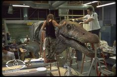 Special character effects artists Joey Orosco and Trevor L. Hensley paint JURASSIC PARK III's enormous animatronic Spinosaurus puppet.