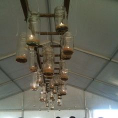 Tealights in canning jars, hanging from a ladder. Dance floor lighting. (at K&K's wedding)