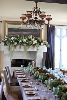 French Country House Flowers, Vela Images, Fireplace mantle decorated with flowers and rectangular table with a flower garland