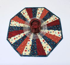 Just in time for the 4th of July! This is a small country style Octagon Patriotic Table Runner Quilt or Candle Mat. Its all in red, tan, and blue and loaded with stars and stripes. This will look great on any flat surface in July, or all summer, or for every patriotic holiday. SIZE: 16 wide side to side, 17 1/2 wide point to point. I have quilted it with wavy lines in every piece. These are the stripes to go with the stars! Binding is a blue and cream print, and the back (seen in the photos)…
