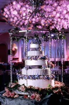 The tall wedding cake was displayed inside of an antique birdacage.