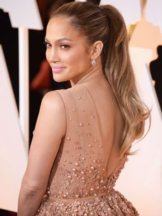 JENNIFER LOPEZ Lopez gets magically younger and better-looking with each passing year. So many aspects of this look are glorious: glowing skin, perfect pink lips, top-notch brows, and a sleek ponytail—because hey, her hair can't compete with that huge gown.