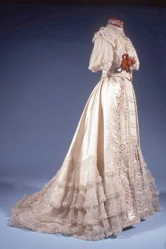 """Dress, Welborn of London, ca. 1905. Cream satin with silk chiffon and crepe de chine trimmed with Honiton and guipure lace, orange velvet, and silver sequins. The pouched bodice (the """"pouter pigeon"""" look) and flared, trained skirt give it the sweeping curves we associate with the Edwardian age."""