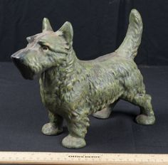 CAST IRON SCOTTIE DOG DOOR STOP. HAS A NICE GREEN PATINA COATING OF PAINT. MEASURES 8 INCHES HIGH AND 10 INCHES LONG