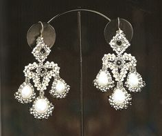 Girandole earrings became fashionable in 17th century Europe when women began to wear their hair up. These multi-pendant earrings are the precursors of chandeliers. Indeed their name comes from the crystal pendant candelabras of the era. The original girandoles were so heavy, some ladies had to attach ribbons from the earrings to their hair to take the weight off their ears!   Book Review, Classical Elegance, The Beading Gem's Journal