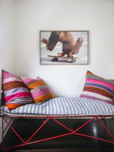striped or graphic pillows on bench behind tulip table.  two additional sculptural looking dining chairs.