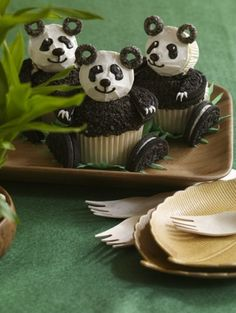 PANDA cupcakes! Mini cupcake laid on its side for head; Oreo-O's cereal for ears; oreo cookie halves for legs (crushed oreos top the big cupcake body)