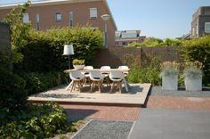 Ontwerp en aanleg tuin in Nieuw-Vennep vlonderterras bangkirai met een ruime eettafel erop, gecombineerd met gebakken klinkerpaden en een keramiek terras www.biesot.nl