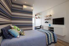 quarto adolescente - Quarto com mobiliário branco + parede listrada em tons de azul. Gosto muito desse recurso para quartos de crianças: base neutra e um detalhe que pode ser facilmente adaptado, no caso o papel de parede. Projeto Evelyn Sayar.