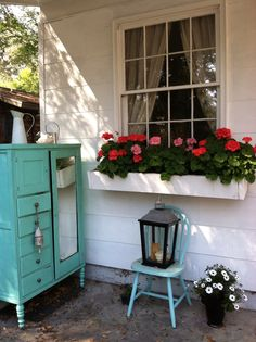 Red and pink geraniums in window box planter. Antique turquoise chifferobe as potting shed.