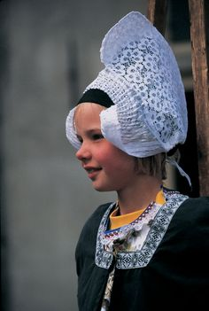 Dutch girl wearing traditional clothes and headdress, Volendam, The Netherlands