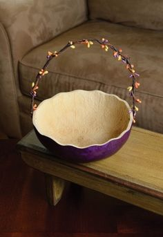 "Retired - This basket is great for sharing your Easter candy, eggs or carrots. The handle is decorated with spring colored berries and the basket has a scalloped edge. This basket is purple in color and approximately 7"" in diameter."