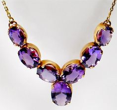 "The necklace is 16"" long with a 1 7/8"" centerpiece of 7 incredibly deep purple amethysts of graduating sizes ie. from 1.5cts to 3cts, with an estimated total carat weight of 14cts. All the amethysts are in open-backed mounts letting their glorious color show to its fullest clarity.    The necklace weighs 7.7grams and is stamped 750 for 18k on both the bale and the chain. The quality of construction is superb and all the stones are in marvelous condition with no chips, cracks or otherwise…"