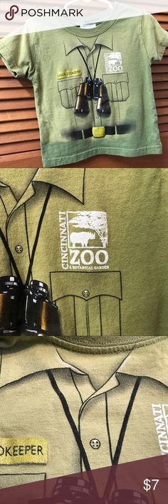 Cincinnati Zoo 'Junior Zookeeper' Tee Shirt Cincinnati Zoo 'Junior Zookeeper' Short Sleeve Tee Shirt. Silk Screened front with Cincinnati Zoo Logo , fake front pockets , belt, collar with buttons down front. There's a gold tag with 'Junior Zookeeper' on it, and binoculars around the neckline. See pictures for fabric and care. In colors of gold, black, white, olive green and shades of green, and brown. Shirts & Tops Tees - Short Sleeve