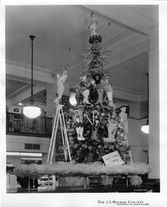 a large christmas tree is displayed atop a retail case the tree is adorned with