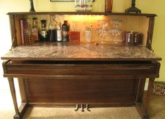 Repurposed Piano Wet Bar: The Piano Wet Bar is made from a vintage upright piano.  Open the door to reveal a lighted cabinet to house your glassware and spirits.  There is also a hidden storage space under the keyboard. This is a unique conversation piece that proves to be both useful and decorative....