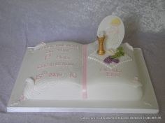 Open bible communion cake finished in pink details and message topped with a sugar challis, wheat and grapes, and girl on plaque