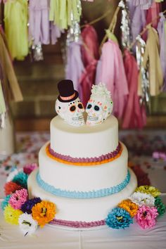 """I hand decorated the wedding toppers which were bride and groom Mexican Day of the Dead skull inspired- I even made a miniature top hat for the groom skull! I also decorated the knife we used to cut the cake with crepe paper and a foiled tassel streamer."
