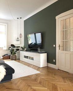 Grüne Wand im Wohnzimmer, stimmig mit braunem Fußboden und hellem Teppich