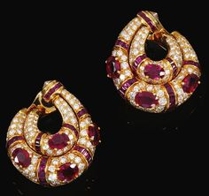 PAIR OF RUBY AND DIAMOND EAR CLIPS, BULGARI. Each designed as two hoops decorated with oval and buff-top rubies, enhanced with brilliant-cut and rose diamonds, signed Bulgari, Italian assay marks, case by Bulgari.