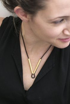 An everyday V shaped necklace on a black Leather necklace cord, allowing the leather chain to thread through the v shaped gold pendant. This long gold pendant gives a futuristic and most unusual look to every item worn with it.