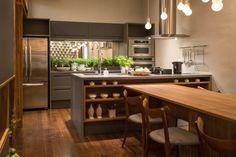 A mesa de jantar é de laminado madeirado, tem 12 lugares e culmina em uma ilha funcional com pia, cooktop e prateleiras.
