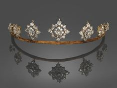 A diamond tiara, necklace and brooch combination once put up for sale by Tennants auctioneers. Circa 1900, designed as a series of seven motfs with diamond cluster centres on a brown velvet band, valued at £10,000 to £12,000.