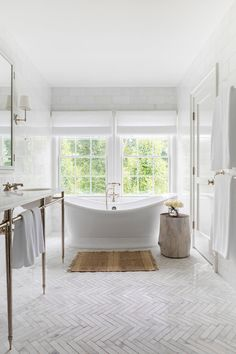A vintage freestanding bathtub sits on thin marble herringbone pattern floor tiles beneath windows covered in white roman shades in this chic white bathroom. Marble Bathroom Floor, Modern Bathroom, Freestanding Bathtub, White Bathrooms, Vintage Bathroom Floor, Best Bathroom Flooring, Bathtub Tile, White Bathroom Tiles, Dyi Bathroom