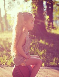 Beautiful little girl loves playing basketball with her long ponytails