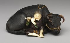 Netsuke: Ox with boy playing flute, 19th century Japanese Wood, ivory, metal
