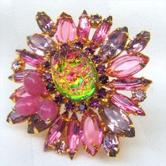 This Beautiful D E Juliana Brooch/ Pendant Features a Large High Domed Pink Green Lava Stone Center with a Small Cluster of Pink Mottled Beads Surrounded by Lavender and Pink Rhinestones, This Brooch Measures 2 1/4 inches Across, Beautiful Gold Plating with a Bale for use a Pendant.