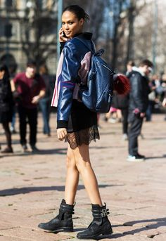 Joan Smalls wearing a black lace trim mini-skirt,  a blue varsity jacket and combat boots with buckle detail, accessorized with a blue leather backpack