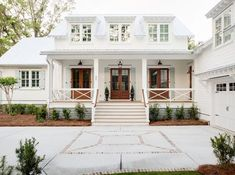 Today's dream home is a pretty coastal farmhouse featuring crisp white wood siding, warm wood french doors, a perfect pop of soft blue on painted shutters, and a metal roof. The home is classic but fr Modern Farmhouse Exterior, Coastal Farmhouse, Modern Farmhouse Style, Farmhouse Design, Coastal Country, Low Country, Coastal Style, French Country, Farmhouse Decor