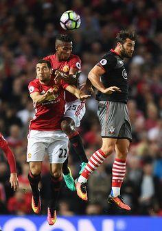 Henrikh Mkhitaryan and Antonio Valencia of Manchester United jump for a header…