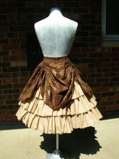 A perfect compliment to any steampunk, anime, or gothic lolita outfit. This adorable overskirt is made with built in ribbon drawstrings allowing you to tie the overskirt up into a variety of bustle fashions. The skirt also features a clip allowing the front to be lifted up to show off your petticoat, bloomers or underskirt. It opens with a hidden side zipper. This fun skirt is constructed from cotton and will be made in your choice of colors and patterns. This is a custom item and takes 6-8…