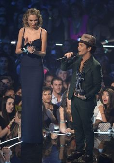 """Taylor Swift presents an award to Bruno Mars - damn no wonder bruno mars was locked out of heaven he couldn't reach the doorknob....""""I'd just like to dedicate this award to all my friends who represent the Lollipop Guild."""""""