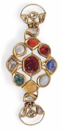 A GEMSET GOLD NAVRATNA BAZUBAND INDIA, 19TH CENTURY Arranged as a floral pattern, with gem-set petal surrounding a gem-set hexagonal pistil, with buckle loop on either side, the reverse enamelled with further floral motifs 3.1/8in. (8cm.) across