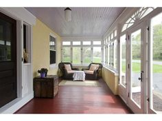 Enclosed porch with painted board floors and ceilings.