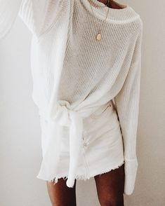 An all white outfit is just as good as an all black outfit. This simple white see through sweater / long sleeve shirt with a tie in the front paired with a white frayed denim skirt and simple gold necklace is the perfect spring outfit.