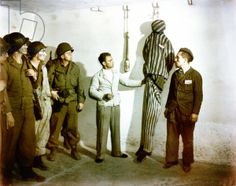 Liberation of Buchenwald Concentration Camp, 18th April 1945. In the crematorium cellar mortuary, former prisoners demonstrate to a group of American GIs how inmates were hanged from hooks on the wall.
